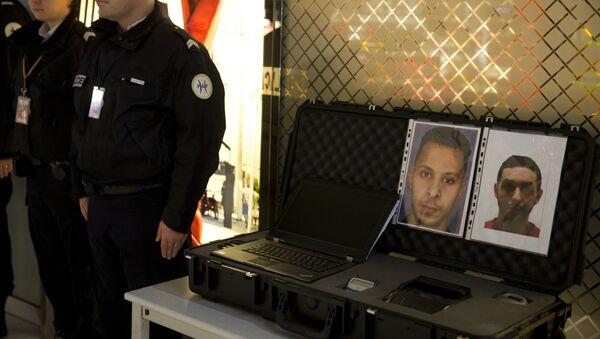 Los agentes de policía están cerca de los retratos de los terroristas Salah Abdeslam y Mohamed Abrini - Sputnik Mundo