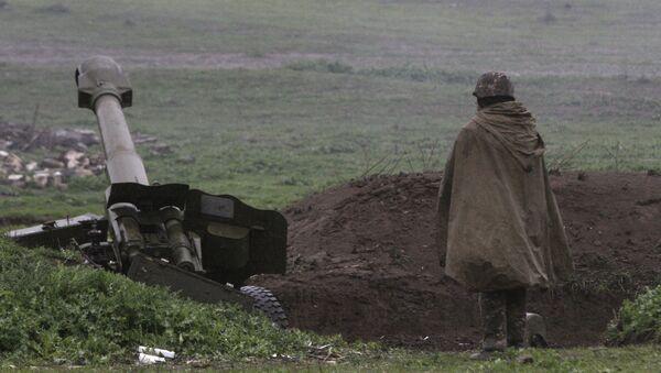 Un soldado de la autodefensa de Nagorno Karabaj cerca de un cañón de artillería - Sputnik Mundo
