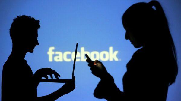 La gente en frente de una pantalla con el logo de Facebook - Sputnik Mundo