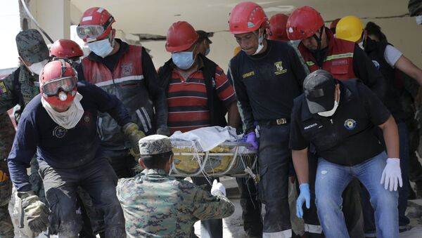 Soldiers and rescue team members carry the body of a victim at a collapsed building after an earthquake struck off the Pacific coast, in Pedernales, Ecuador - Sputnik Mundo