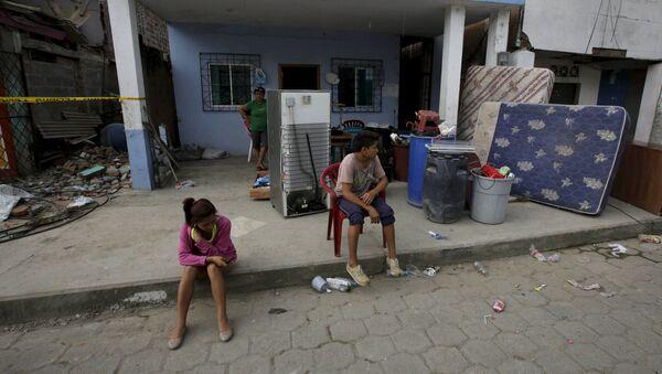 Ecuatorianos en frente de la casa en ruinas - Sputnik Mundo