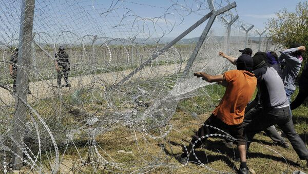 Migrants try to bring down part of a border fence as Macedonian police stand guard at a makeshift camp for refugees and migrants at the Greek-Macedonian border near the village of Idomeni - Sputnik Mundo