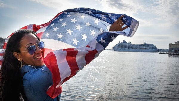 A Cuban waves a US flag at the Malecon waterfront as the first US-to-Cuba cruise ship to arrive in the island nation in decades glides into the port of Havana, on May 2, 2016. - Sputnik Mundo