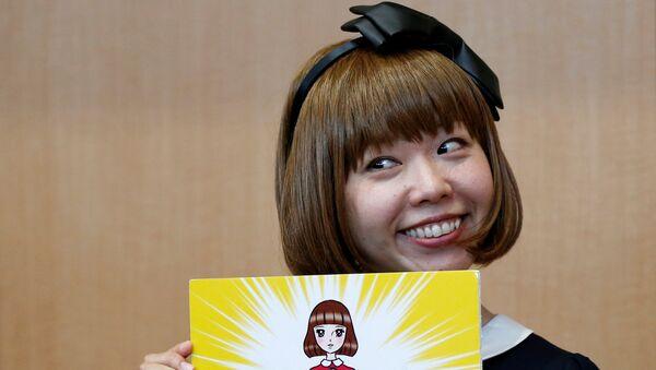 Japanese artist Megumi Igarashi, known as Rokudenashiko, holds her artwork after a news conference following a court appearance in Tokyo - Sputnik Mundo