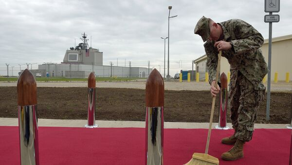 US Army personnel cleans the red carpet ahead an inauguration ceremony of the US anti-missile station Aegis Ashore Romania (in the background) at the military base in Deveselu, Romania on May 12, 2016 - Sputnik Mundo