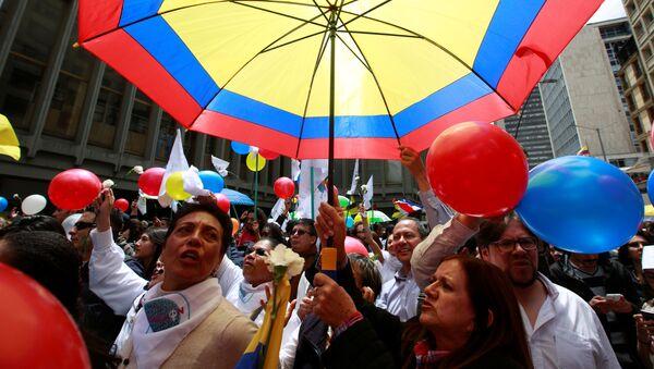 Colombianos celebrando con un paraguas con los colores de su bandera - Sputnik Mundo