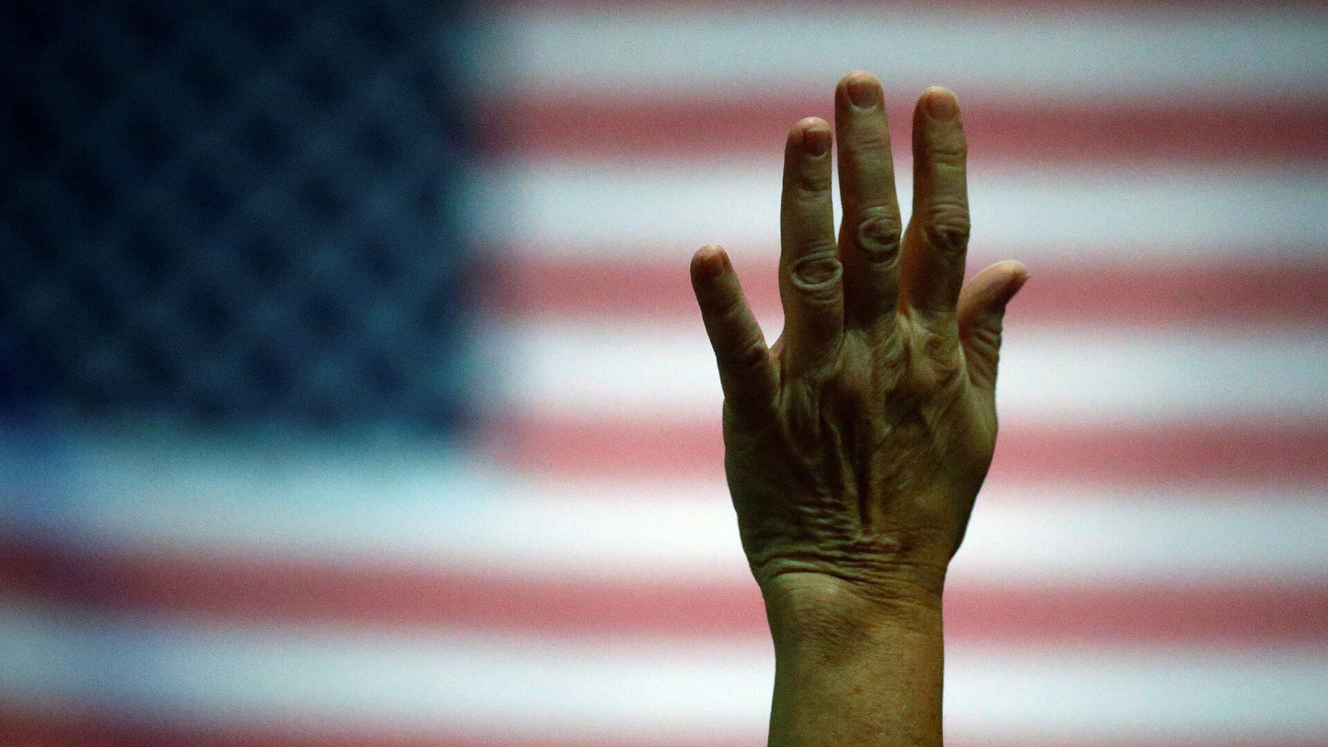Partidario del candidato presidencial Donald Trump levanta la mano durante un evento de la campaña electoral - Sputnik Mundo, 1920, 01.08.2021