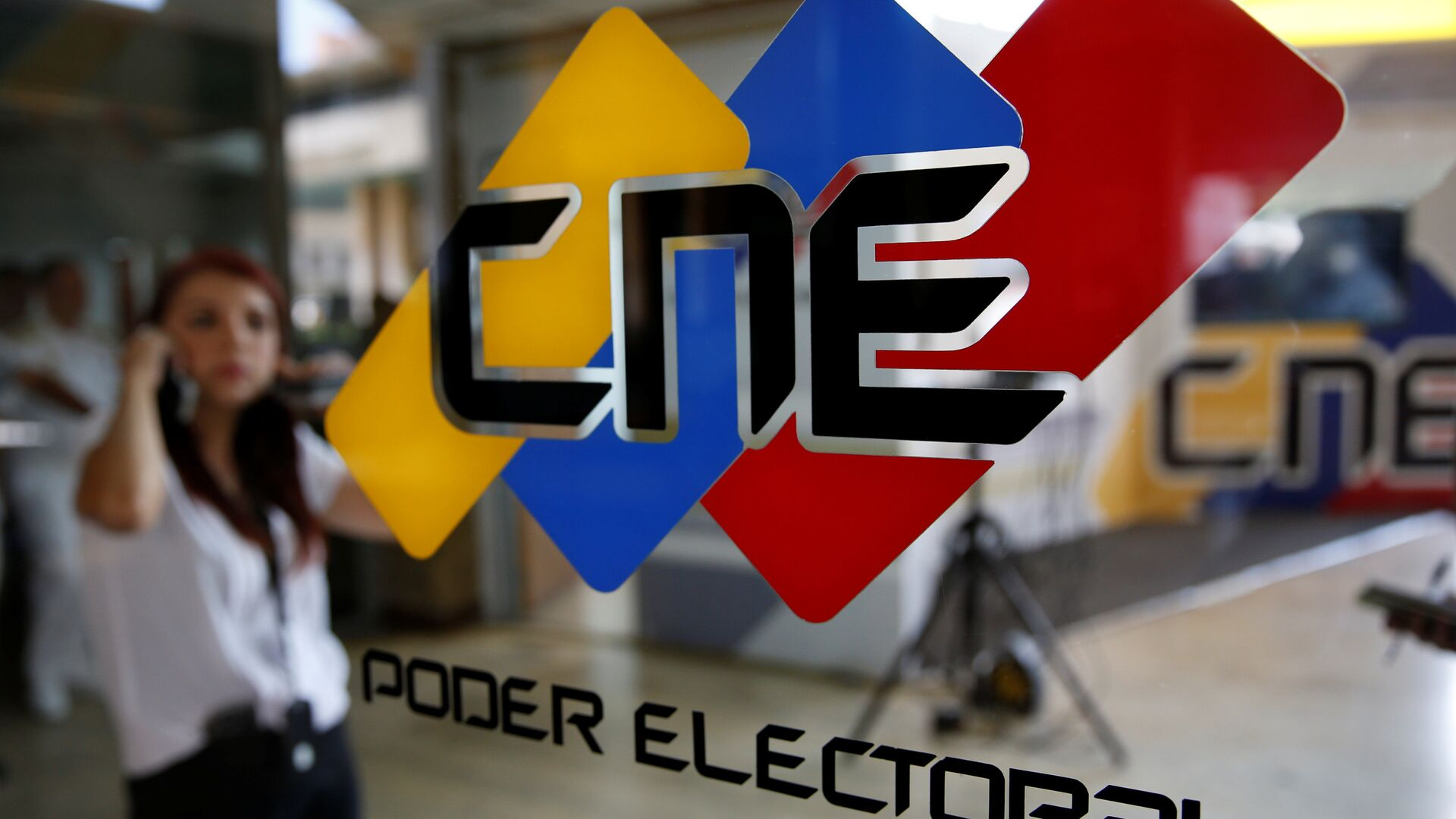 People walk past a logo of the National Electoral Council (CNE) at its headquarters in Caracas - Sputnik Mundo, 1920, 09.08.2021