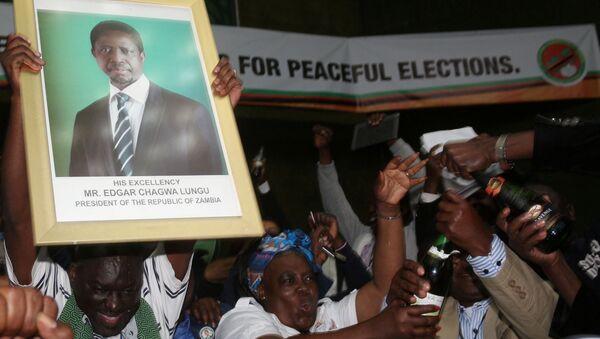 El retrato de reeligido presidente de Zambia, Edgar Lungu, en las manos de sus partidarios - Sputnik Mundo
