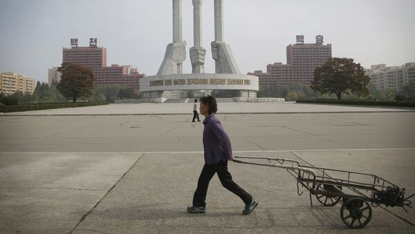 North Korean women walk past a monument built 11 years ago to honor the founding of the Workers' Party of North Korea on Saturday, Oct. 15, 2016, in Pyongyang, North Korea - Sputnik Mundo
