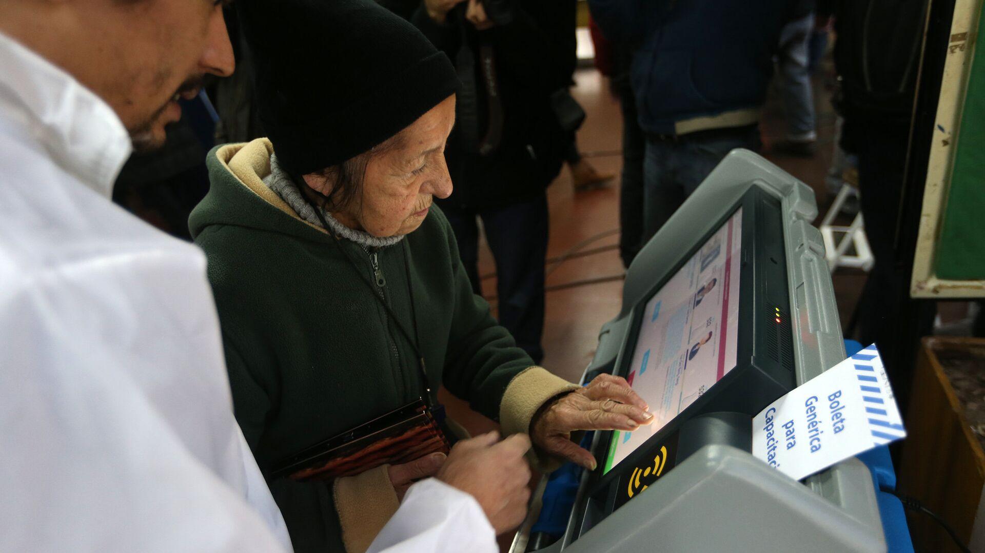 Una anciana argentina usando una máquina de voto electrónico (archivo) - Sputnik Mundo, 1920, 17.08.2021