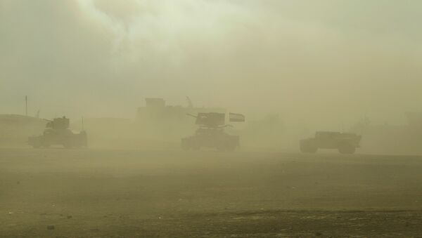 Iraqi army vehicles drive through fumes from a nearby sulfur plant set alight by Islamic State militants, at south of Mosul in Qayyara - Sputnik Mundo