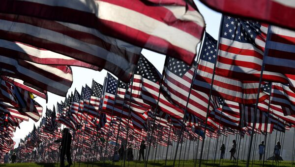 People walk amongst US national flags erected by students and staff from Pepperdine University as they pay their respects to honor the victims of the September 11, 2001 attacks in New York, at their campus in Malibu, California - Sputnik Mundo