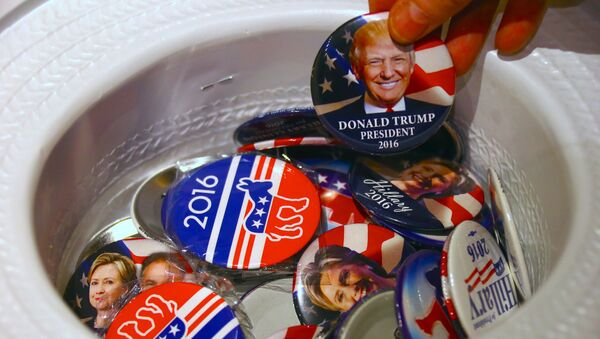 A guest at an event called the U.S. Presidential Election Watch, organised by the U.S. Consulate, reaches for a badge from out of a hat displaying photographs of Republican candidate Donald Trump and Democratic candidate Hillary Clinton, in Sydney, Australia - Sputnik Mundo