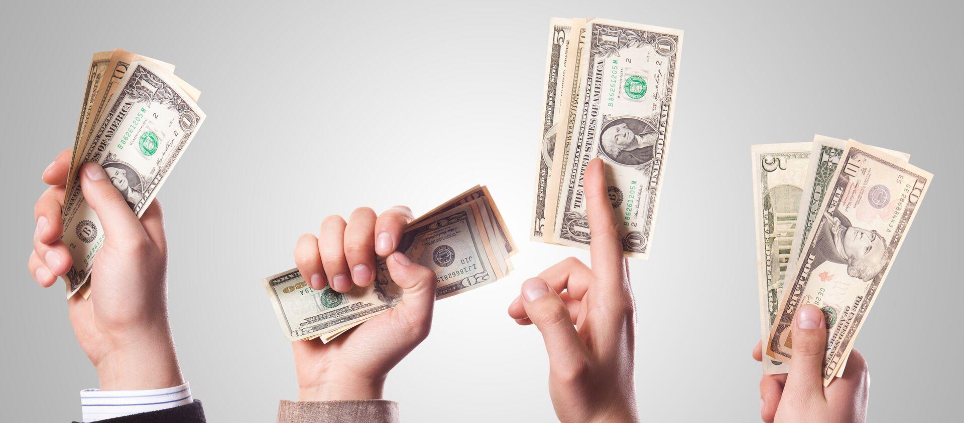 Varias personas con billetes de dólares en las manos - Sputnik Mundo, 1920, 03.02.2021
