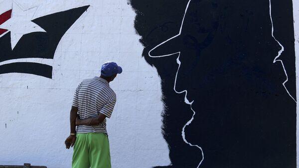A man looks at a mural representing Cuba's late President Fidel Castro in the outskirts of Santiago de Cuba - Sputnik Mundo