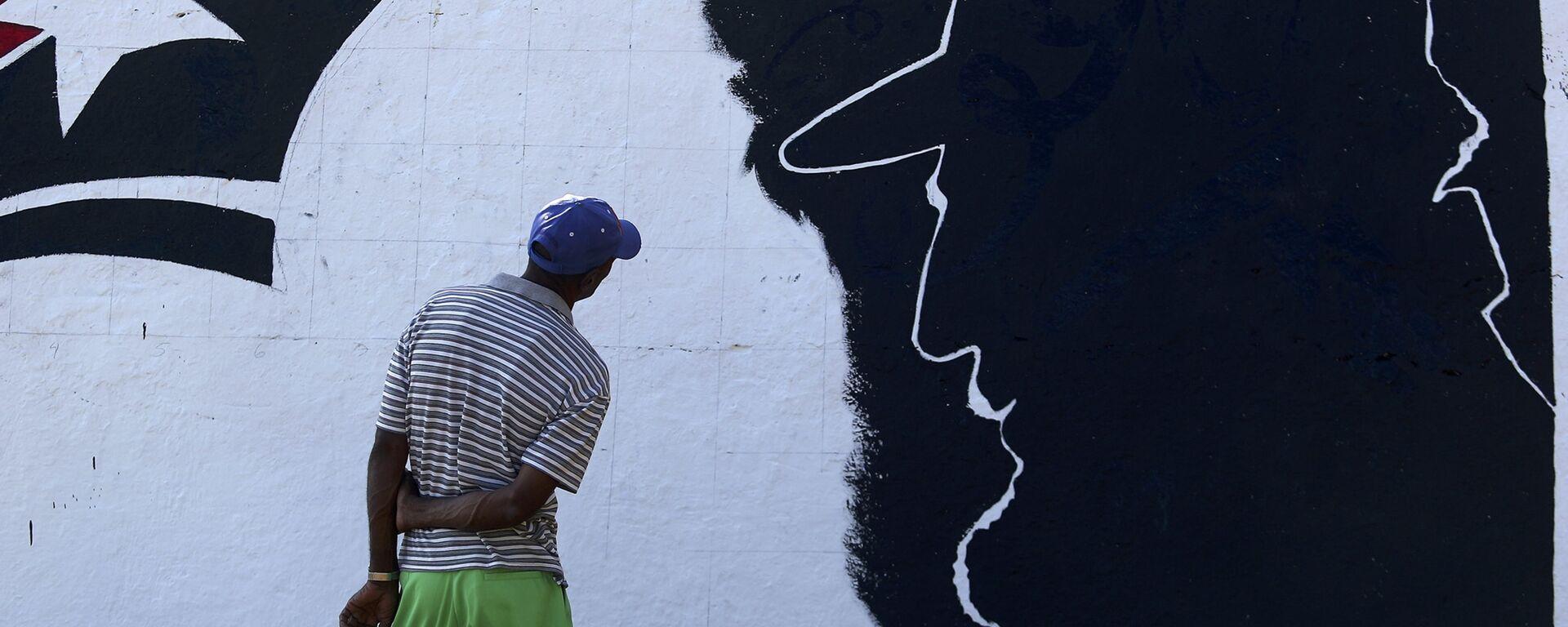 A man looks at a mural representing Cuba's late President Fidel Castro in the outskirts of Santiago de Cuba - Sputnik Mundo, 1920, 13.08.2021