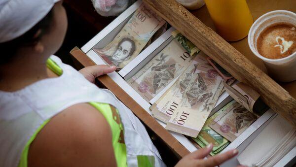 A cashier receives Venezuelan bolivar notes at a market in downtown Caracas, Venezuela - Sputnik Mundo