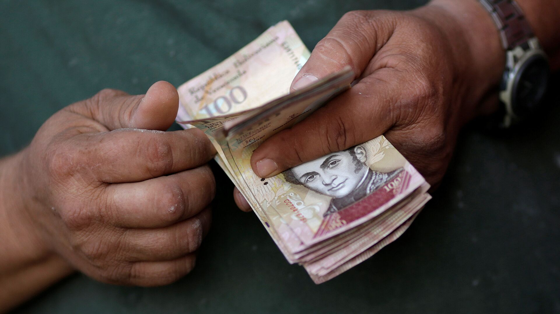 A cashier counts Venezuelan bolivar notes at a street market in downtown Caracas - Sputnik Mundo, 1920, 22.09.2021