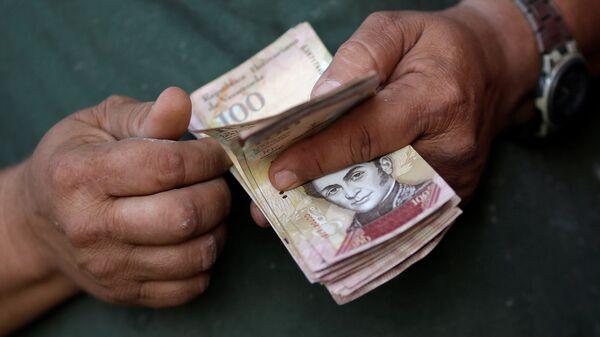 A cashier counts Venezuelan bolivar notes at a street market in downtown Caracas - Sputnik Mundo