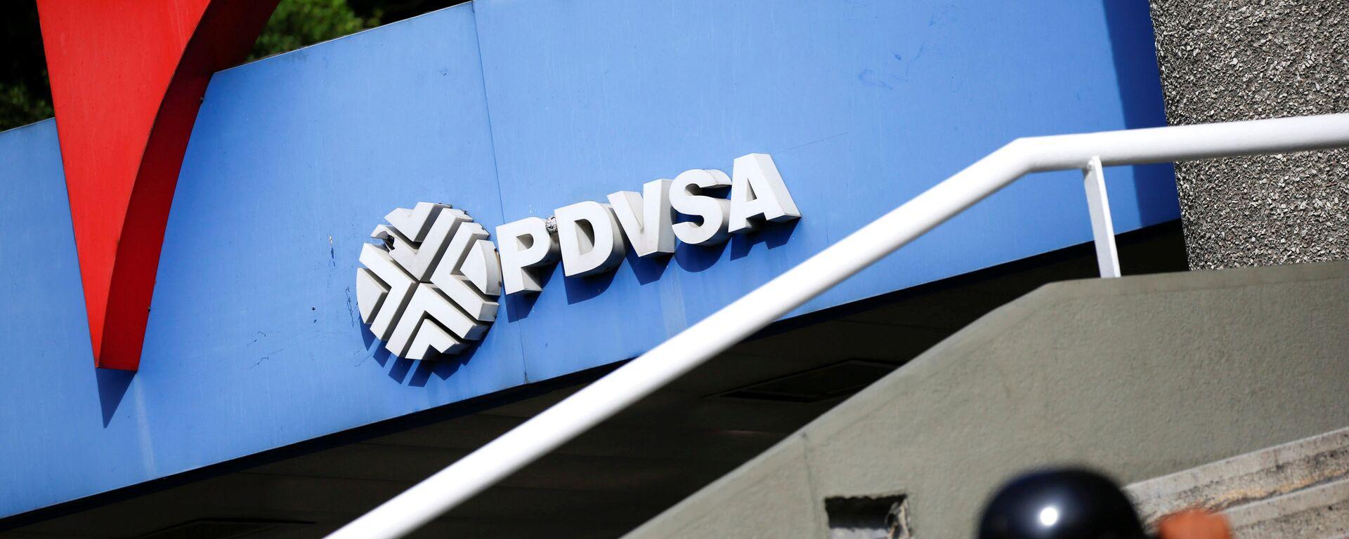 A man walks past a gas station with the logo of the Venezuelan state oil company PDVSA in Caracas, Venezuela December 23, 2016. REUTERS/Carlos Garcia Rawlins - Sputnik Mundo, 1920, 02.02.2021