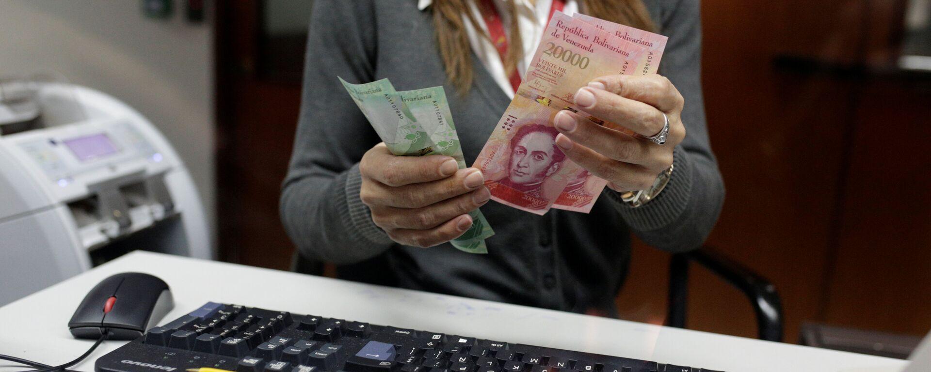 A bank teller counts bolivar banknotes at a Banco de Venezuela branch in Caracas - Sputnik Mundo, 1920, 21.01.2021