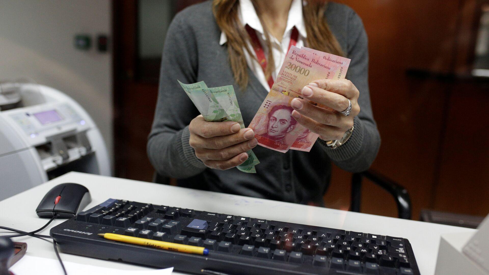 A bank teller counts bolivar banknotes at a Banco de Venezuela branch in Caracas - Sputnik Mundo, 1920, 27.09.2021