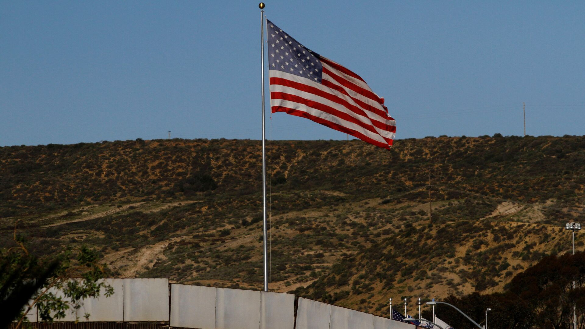 A U.S. flag is seen next to a section of the wall separating Mexico and the United States, in Tijuana, Mexico, January 28, 2017 - Sputnik Mundo, 1920, 13.10.2021