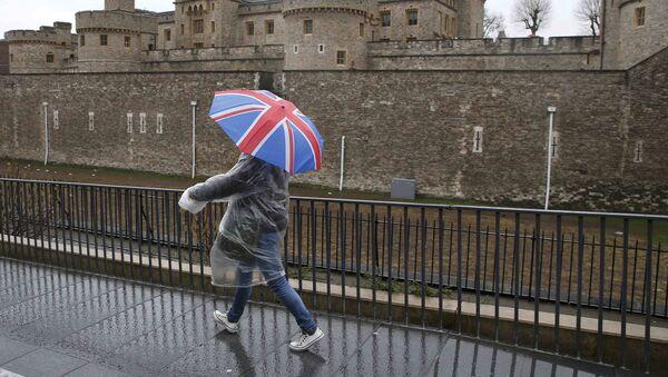 Una persona lleva un paraguas con la bandera de Reino Unido (imagen referencial) - Sputnik Mundo