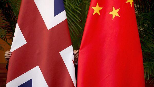 A worker adjusts British and China (R) national flags - Sputnik Mundo