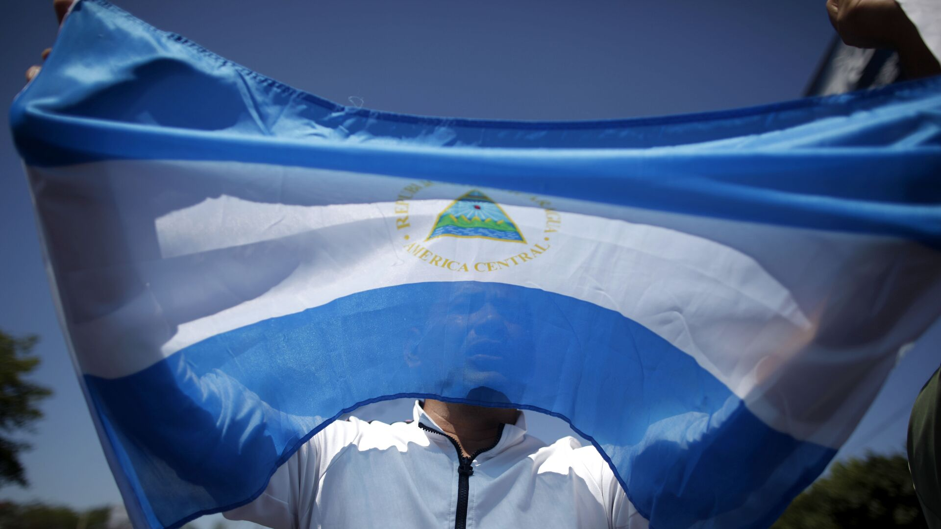 A man holds up a Nicaraguan flag during a demonstration against the presidential candidacy of Nicaragua's President Daniel Ortega in Managua, Nicaragua, Sunday, Feb 20, 2011.  - Sputnik Mundo, 1920, 07.09.2021