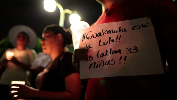 A man holds a banner that reads Guatemala is in mourning. we are missing 33 girls during a vigil for victims of a fire at the Virgen de Asuncion home in Guatemala, in Managua, Nicaragua - Sputnik Mundo