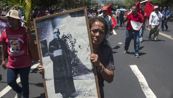 Una mujer sostiene retrato del Monseñor Óscar Romero asesinado en la década de los 80 - Sputnik Mundo