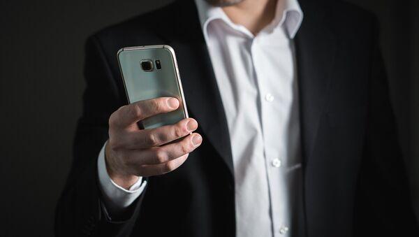 Un hombre con su smartphone - Sputnik Mundo
