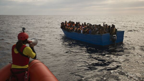 Migrants and refugees are assisted by members of the Spanish NGO Proactiva Open Arms, as they crowd aboard a boat sailing out of control in the Mediterranean Sea about 21 miles north of Sabratha, Libya, on Friday, Feb. 3, 2017. European Union leaders are poised to take a big step on Friday in closing off the illegal migration routes from Libya across the central Mediterranean, where thousands have died trying to reach the EU, the EU foreign affairs chief Federica Mogherini said. - Sputnik Mundo