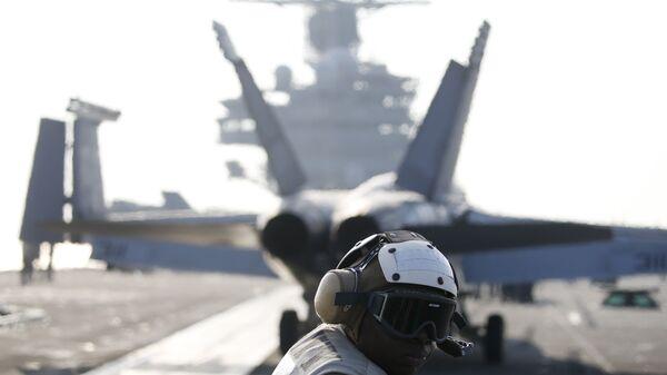 Un miembro de la tripulación de la Marina estadounidense al lado del caza F / A-18 Super Hornet que se prepara para despegar del USS Ronald Reagan, portaaviones de la clase Nimitz de propulsión nuclear - Sputnik Mundo