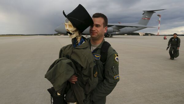 Eric Kordus, a F-22 Raptor fighter jet pilot of the 95th Fighter Squadron from Tyndall, Florida, carries Mr. Bone, the squadron's mascot consisting of a dressed-up plastic skeleton with a stovepipe hat and a moustache, after a refuelling mission of a KC-135 Stratotanker from the NATO airbase of Aemari, Estonia to Spangdahlem, Germany September 4, 2015 - Sputnik Mundo
