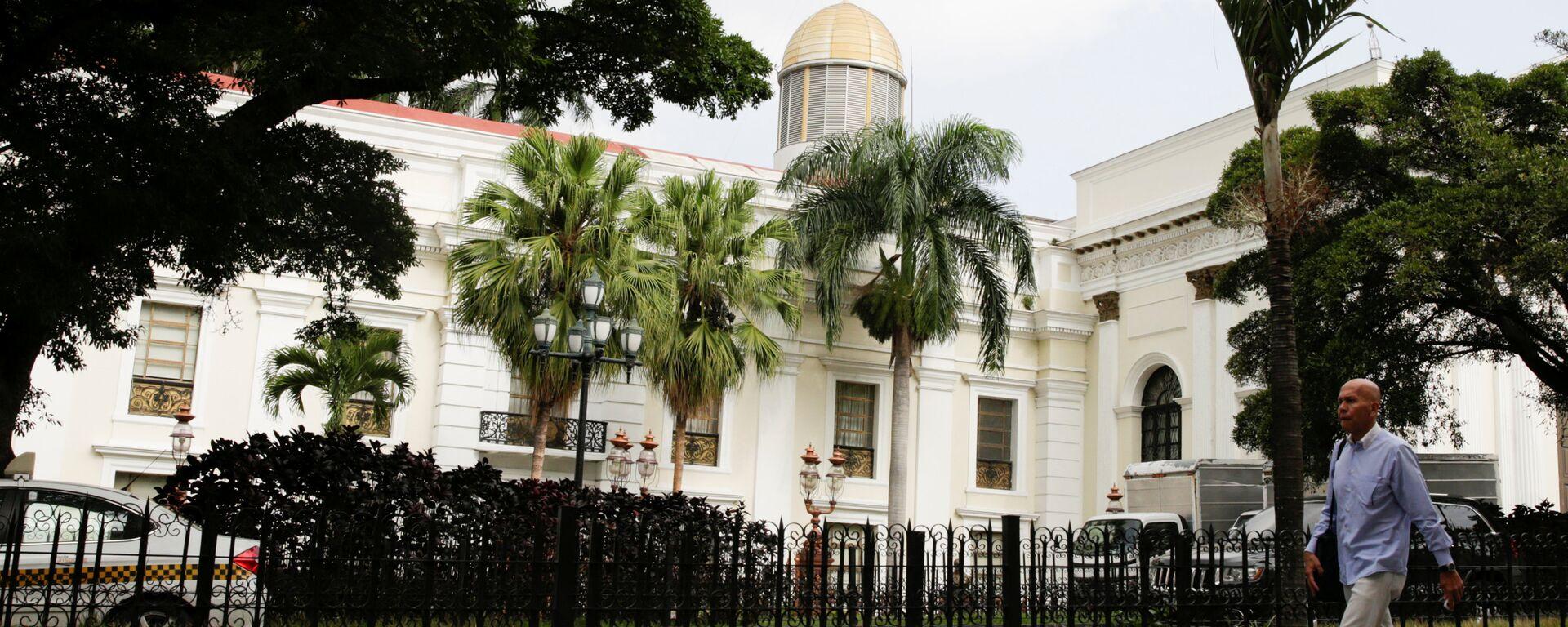 A man walks past the building of the National Assembly in Caracas, Venezuela - Sputnik Mundo, 1920, 14.01.2021