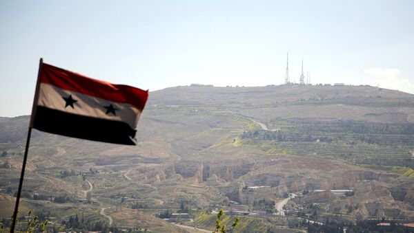 A Syrian national flag flutters as Qasioun mountain is seen in the background from Damascus, Syria April 7, 2017 - Sputnik Mundo