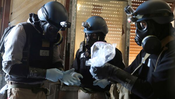 A U.N. chemical weapons expert, wearing a gas mask, holds a plastic bag containing samples from one of the sites of an alleged chemical weapons attack in the Ain Tarma neighbourhood of Damascus, Syria. (File) - Sputnik Mundo