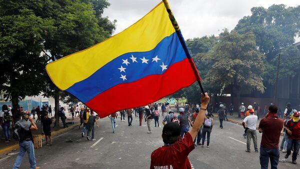 Un manifestante con la bandera de Venezuela - Sputnik Mundo