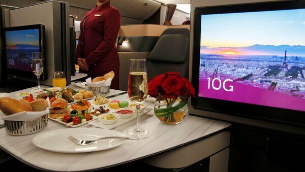 Azafata de Qatar Airways presenta asientos de la primera clase de un Boeing 777 - Sputnik Mundo