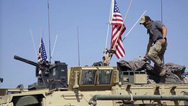 Soldado estadounidense sobre un vehículo blindado en la aldea de Darbasiyah, norte de Siria. - Sputnik Mundo
