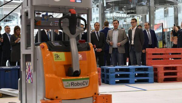 El fundador de RoboCV, Serguéi Máltsev (traje gris), presenta su robot-montacargas al primer ministro ruso, Dmitri Medvedev (a la izquierda de Máltsev) - Sputnik Mundo