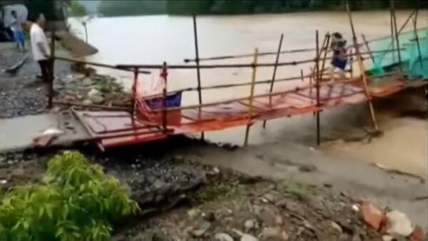 Una china salva la vida tras huir por un puente que poco después fue arrasado por las aguas - Sputnik Mundo