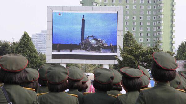 Los norcoreanos observan en una pantalla el lanzamiento del misil balístico - Sputnik Mundo
