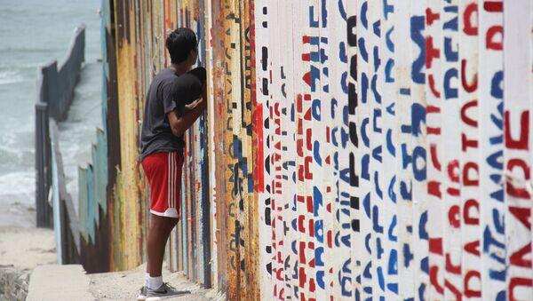 Un joven habla con sus familiares a través del muro que separa México y EEUU - Sputnik Mundo