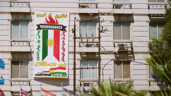 El cartel con la bandera de Kurdistán iraquí - Sputnik Mundo