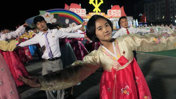 North Korean men and women participate in a mass dance event marking the 20th anniversary of the election of former leader Kim Jong Il as general secretary of the Workers' Party, which is the founding and ruling party of North Korea, at Kim Il Sung Square in Pyongyang, Sunday, Oct. 8, 2017 - Sputnik Mundo