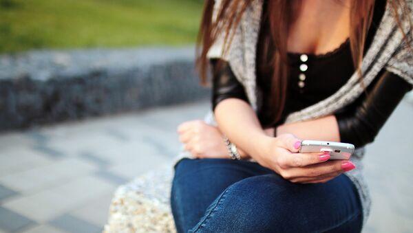 Una mujer escribe mensajes desde su móvil (imagen ilustrativa) - Sputnik Mundo